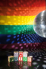 Blocks spelling out gay pride under light of disco ball