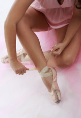 closeup on ballerina tying tip shoes