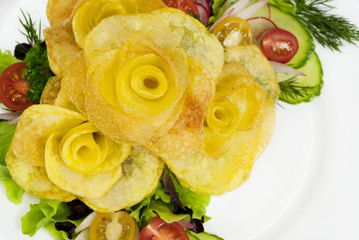French fries in the form of a rose on a plate with a salad
