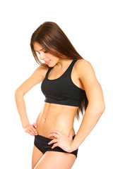 Athletic girl looking at her belly on a white background