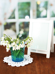 Bouquet of snowdrop flowers in glass vase,