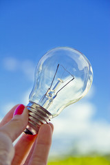 female hand holding lightbulb, business vision