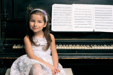 Cute 5 year old girl sitting by piano