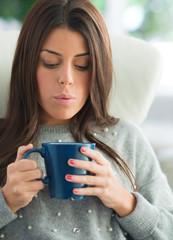 Woman Blowing In Coffee Mug