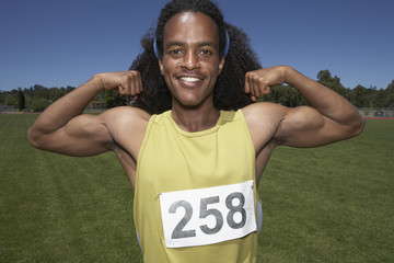 Male track athlete flexing biceps