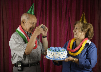 Man photographing woman holding cake