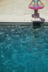 Low section of girl standing on diving board with innertube