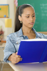 Female Dominican teenager reading a textbook in classroom