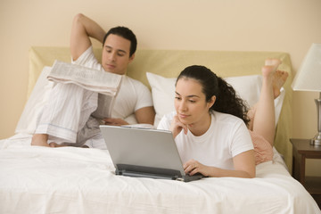 Hispanic couple lying on the bed reading and using a laptop