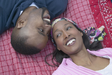High angle view of African couple laying on blanket