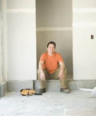 Male carpenter working sitting inside construction site