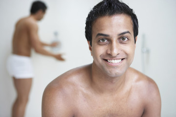 Indian man with bare chest smiling while man in underwear tests shower in background
