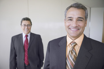 Portrait of Hispanic businessman with coworker in background
