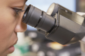 African female scientist looking into microscope