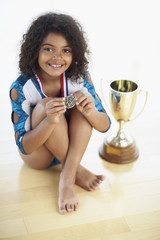 Young female gymnast with medal and trophy