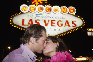 Couple kissing in front of neon sign