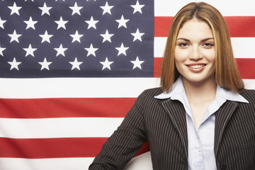 Hispanic businesswoman in front of American flag