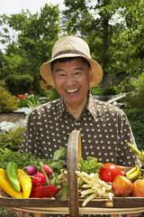 Senior Asian man holding basket of vegetables