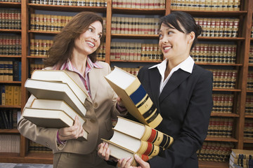 Multi-ethnic women carrying stacks of library reference books