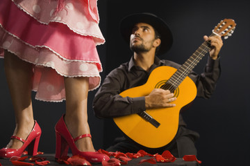 Hispanic female flamenco dancer next to guitar player