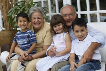 Hispanic grandparents hugging grandchildren