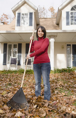Hispanic woman raking leaves