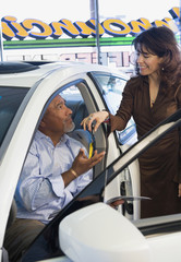 Hispanic man receiving keys for new car at dealership