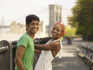 Multi-ethnic couple standing at urban waterfront