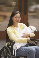 Asian mother in wheelchair with newborn baby