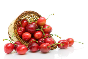 ripe cherry in a wicker basket on a white background close-up.