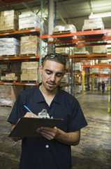 Hispanic man writing on clipboard in warehouse