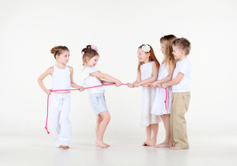 Five cute little children in white clothes draw over pink rope.