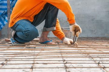 Worker, rebar gridwork across a floor for strength