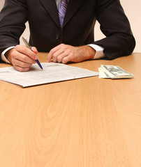Businessman sitting on the desk with  money