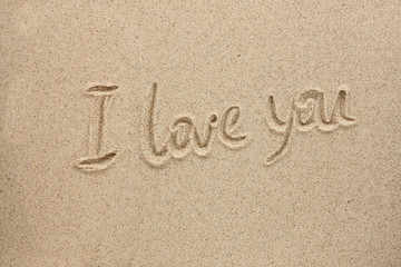 The word i love you written on the sand