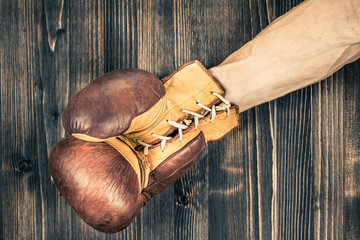 Boxer's hand with leather boxing glove near wood background
