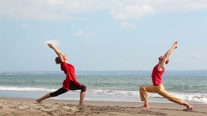 Wall Mural - Peaceful pair practicing yoga together on beach