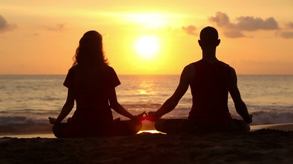 Wall Mural - Couple sitting yoga on beach while sunset