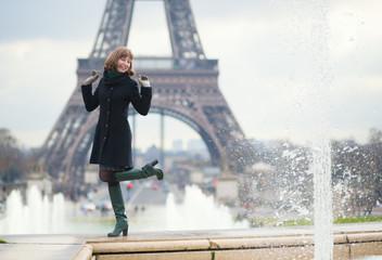 Cheerful girl near the Eiffel tower in Paris