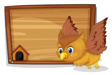 A flying owl beside a wooden blank board