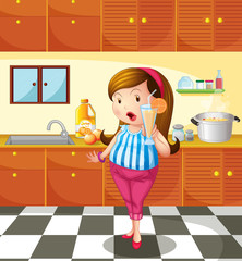A lady holding an orange juice inside the kitchen