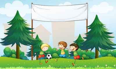 Three boys playing soccer below an empty banner