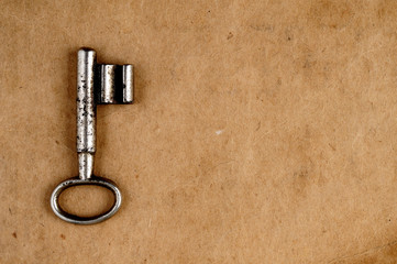 Vintage key on old paper background