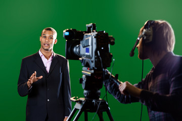 Presenter in studio with TV camera and Camera Operator