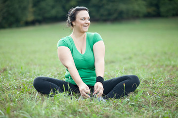Cheerful plus sized woman stretching in the park. Selective focu