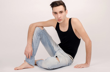 Attractive man in ripped jeans and black top chilling.
