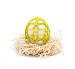 Easter egg  in a nest. Yellow ornament is knitted