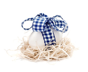 White egg in a nest with blue ribbon and bow