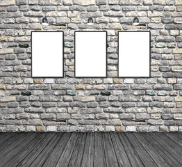 three empty white frames on a brick wall in the room
