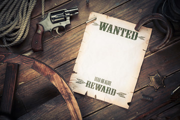 Old wanted poster on wood with vintage objects